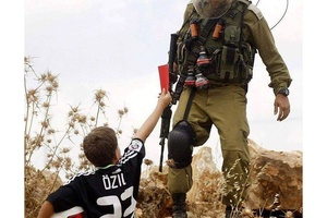 A brave young Palestinian shows the red card to an Israeli soldier for trying to stop kids playing f