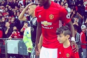 CLASS: Paul Pogba flies over a young Juventus fan to be his Manchester United mascot on his return d
